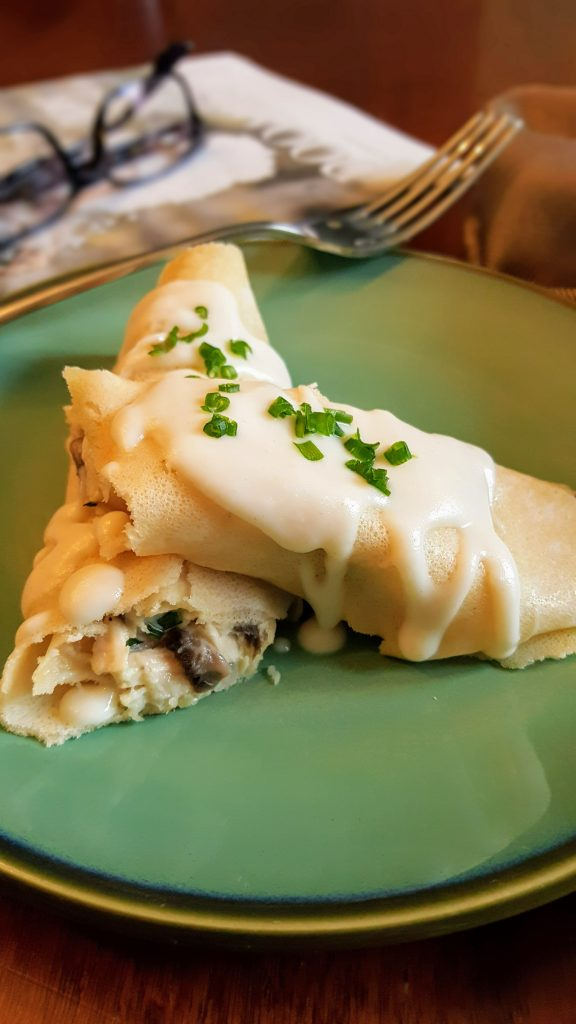 Chicken and Mushroom Crepes with Cream Sauce on a green plate