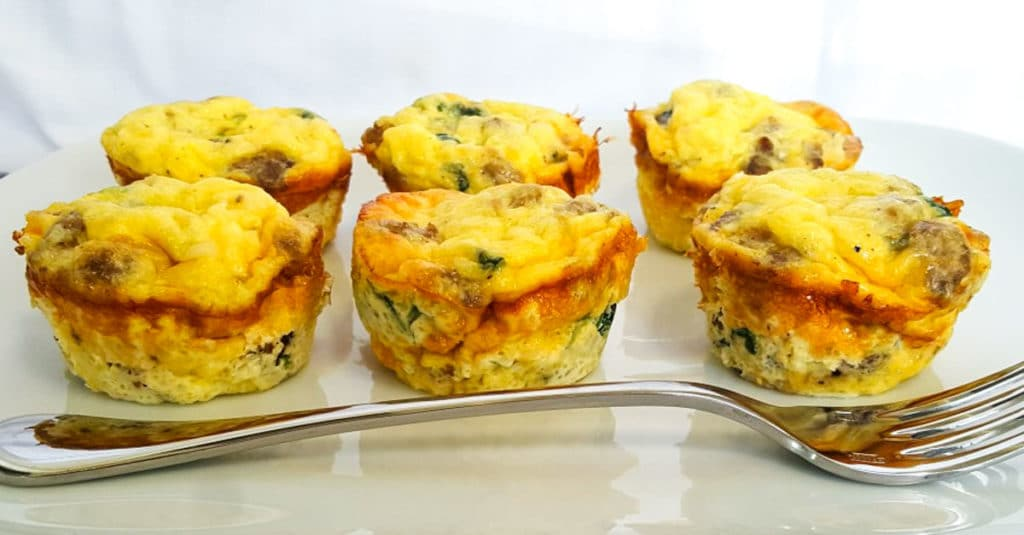 Make Ahead Sausage Egg cups sitting on a white plate with a fork in front
