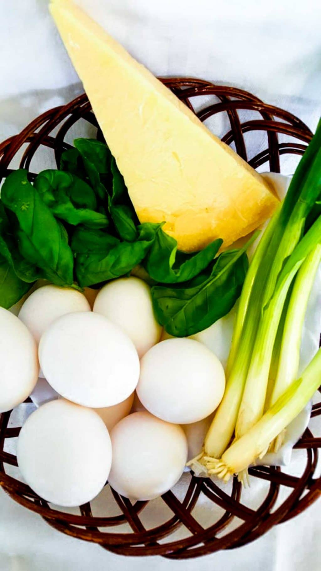 A basket full of eggs, Parmesan cheese, spinach and green onions