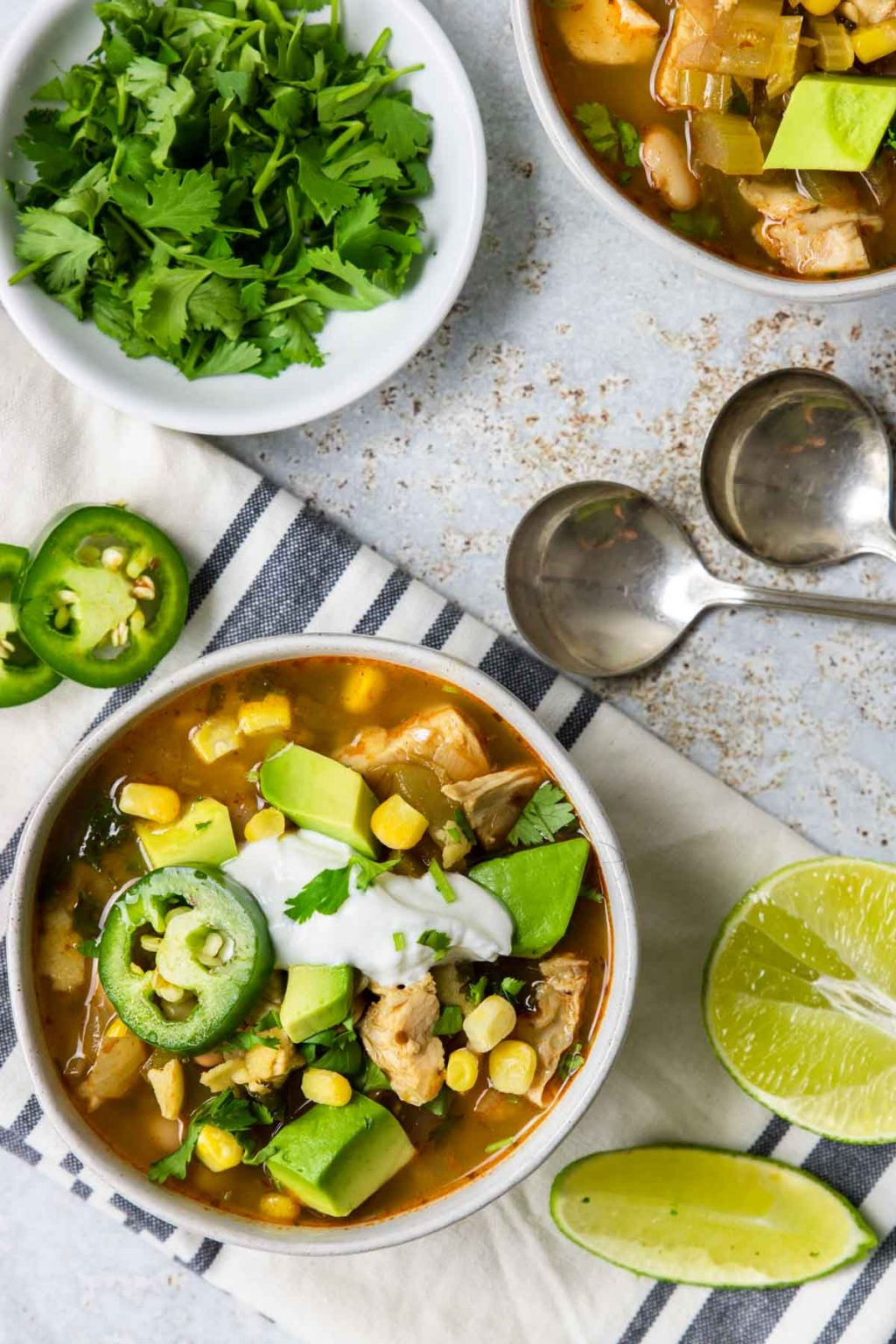 white chicken chili in a white bowl garnished with jalapenos and sour cream