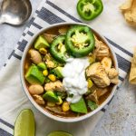 square photo of a bowl of white chicken chili topped with avocado, sour cream, fresh jalapeno and cilantro