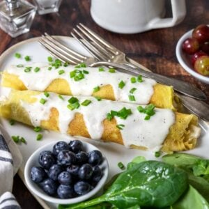 two chicken crepes topped with cream sauce