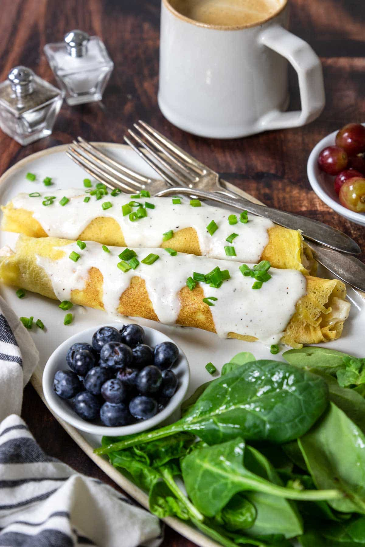 a plate with two chicken crepes topped with béchamel sauce and salad and berries