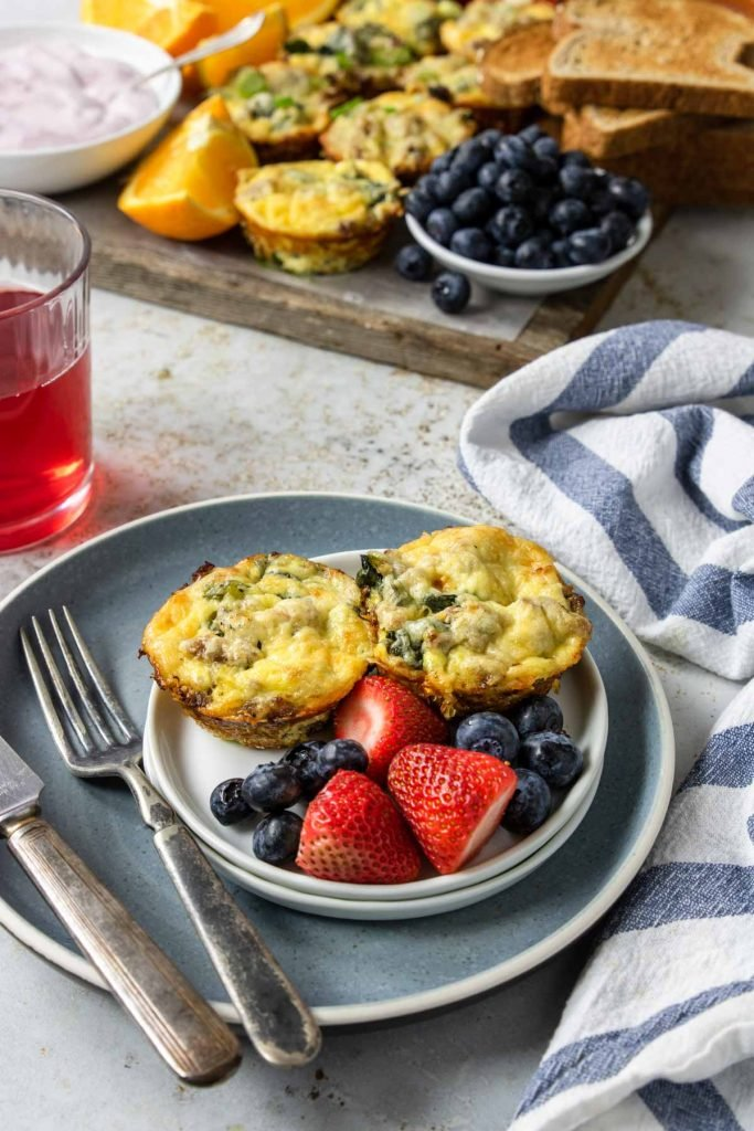 sausage egg muffins on a plate with fresh fruit