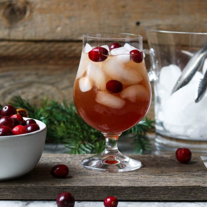 cranberry wine spritzer in a glass garnished with cranberries and a bucket of ice