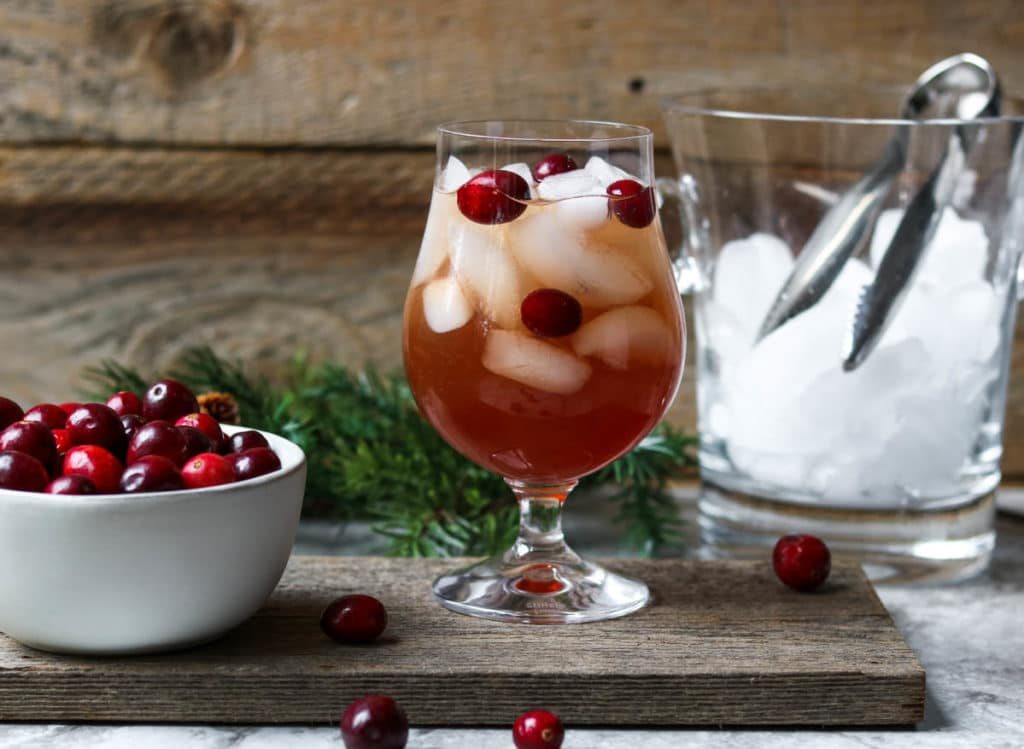 A cranberry white wine spritzer garnished with fresh cranberries, a white bowl of cranberries to the side