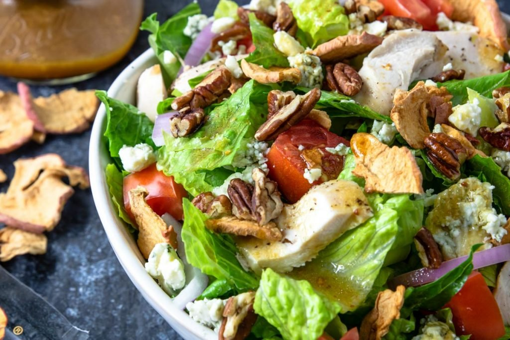 Apple Pecan Chicken Salad in a white bowl with dressing and apple chips to the side