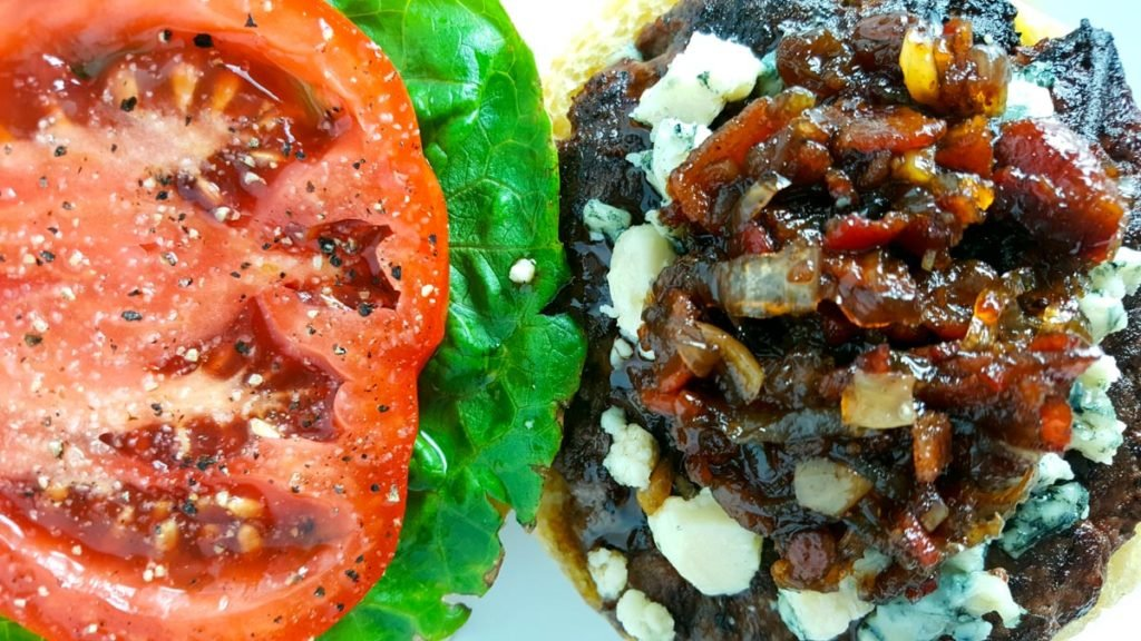 A burger topped with blue cheese and bacon jam on the right, lettuce and tomato on the left