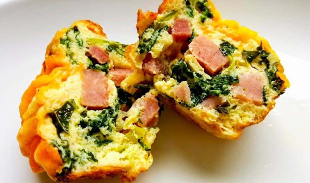 ham and kale egg cup split open so you can see the ham and kale inside