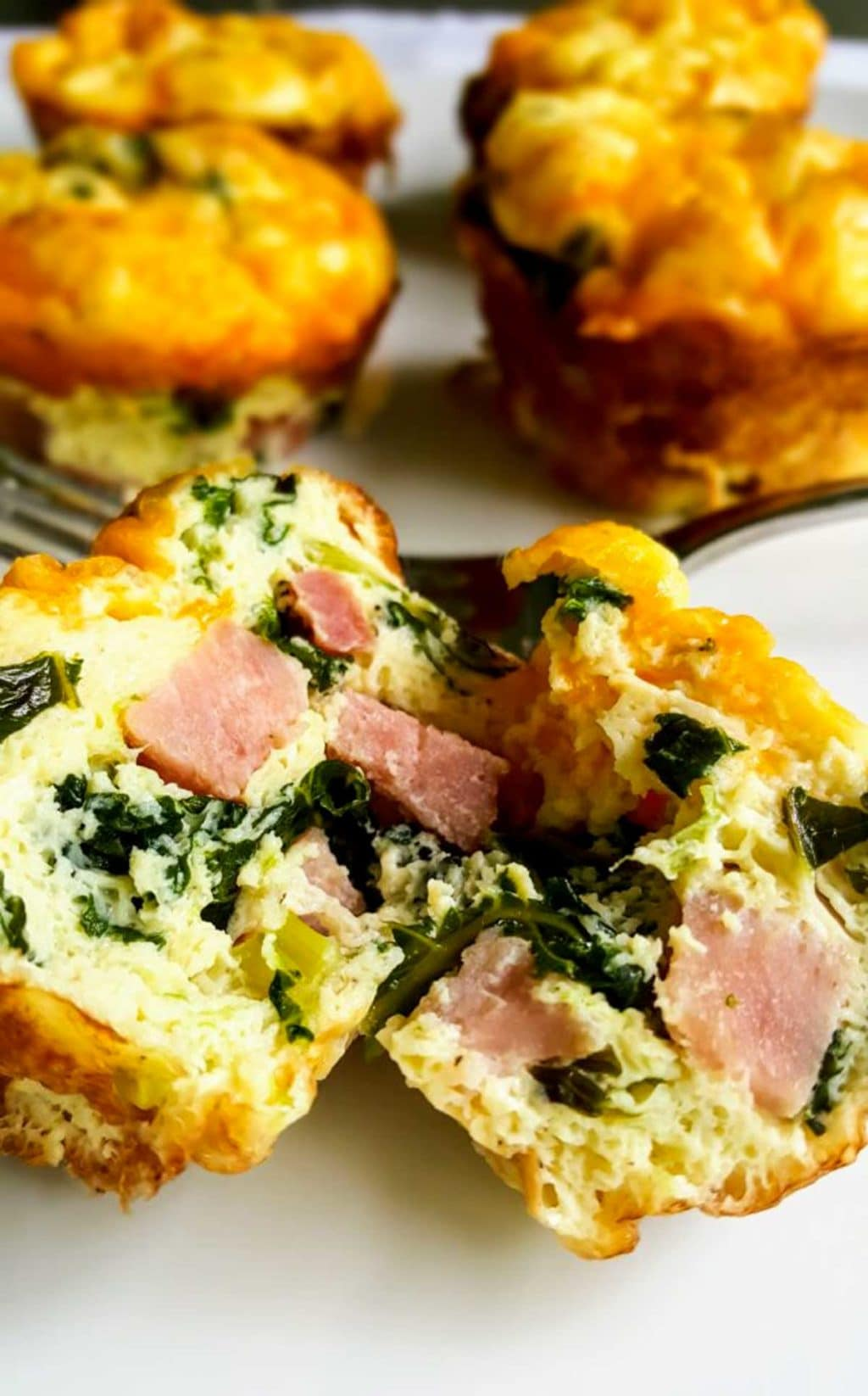 Ham and Kale Egg Cup split in half showing the ham and kale inside