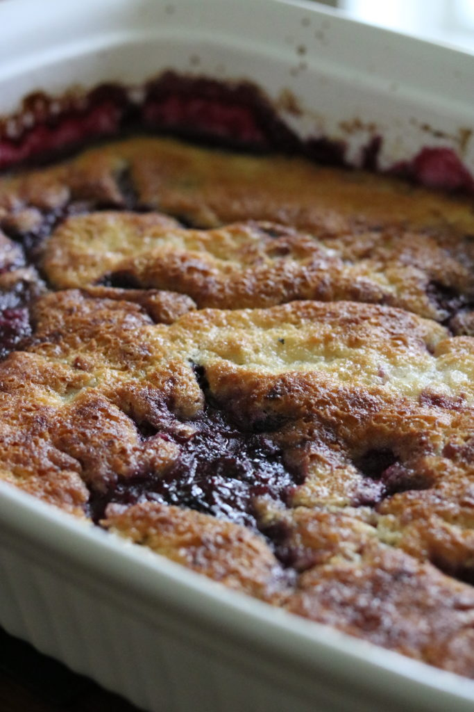 summer berry cobbler baked in a white baking dish momsdinner.net