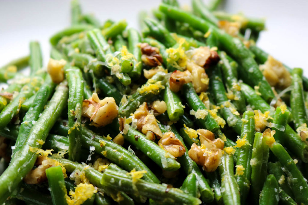 green beans topped with nuts and lemon zest