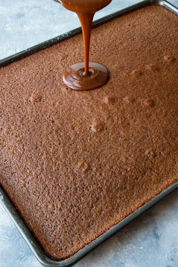 step 1 frosting being poured onto chocolate cake