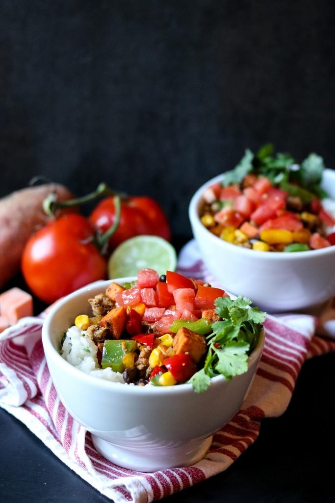 two white bowls of Southwest Sweet Potato & Turkey tomatoes and limes in the background