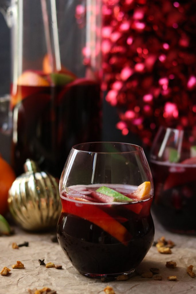 A glass of winter sangria mixed with fruit, holiday decorations in the background