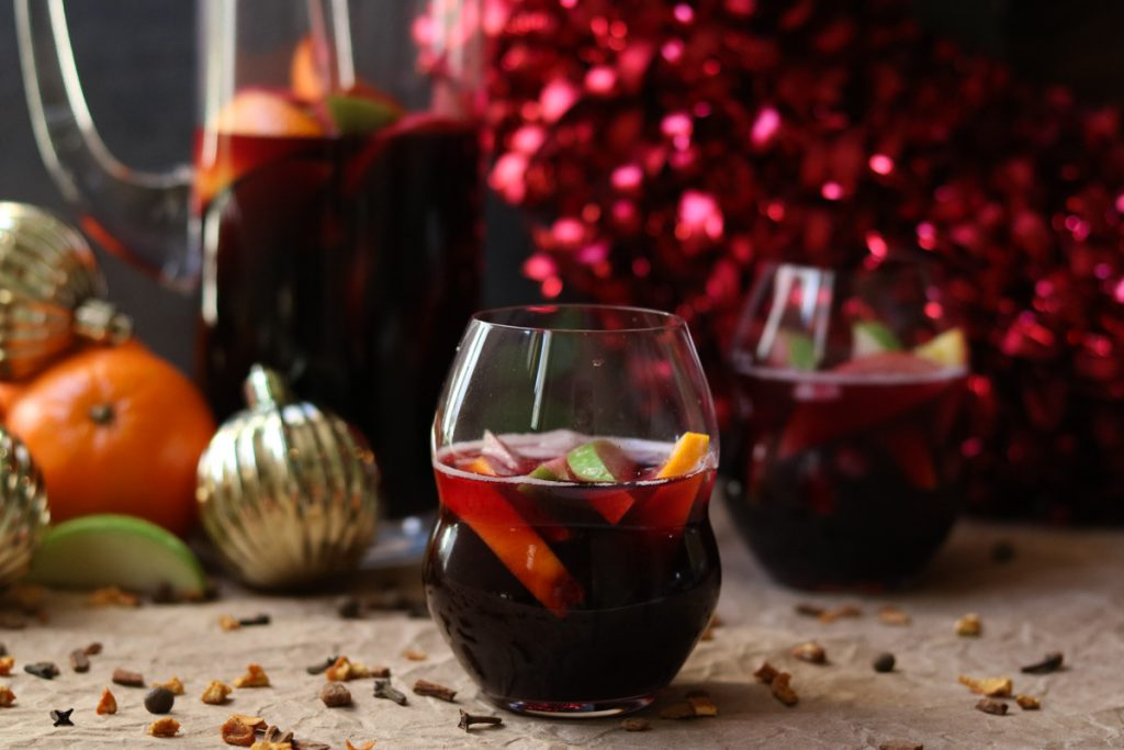 A glass of Red Wine Winter Sangria mixed with oranges and apples. Holiday decor and a pitcher of winter sangria are in the background.