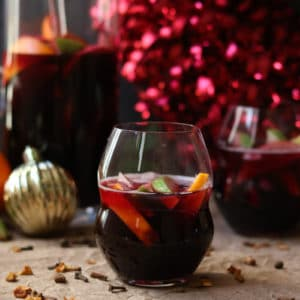 a glass of winter sangria red wine surrounded by citrus fruit and christmas ornaments