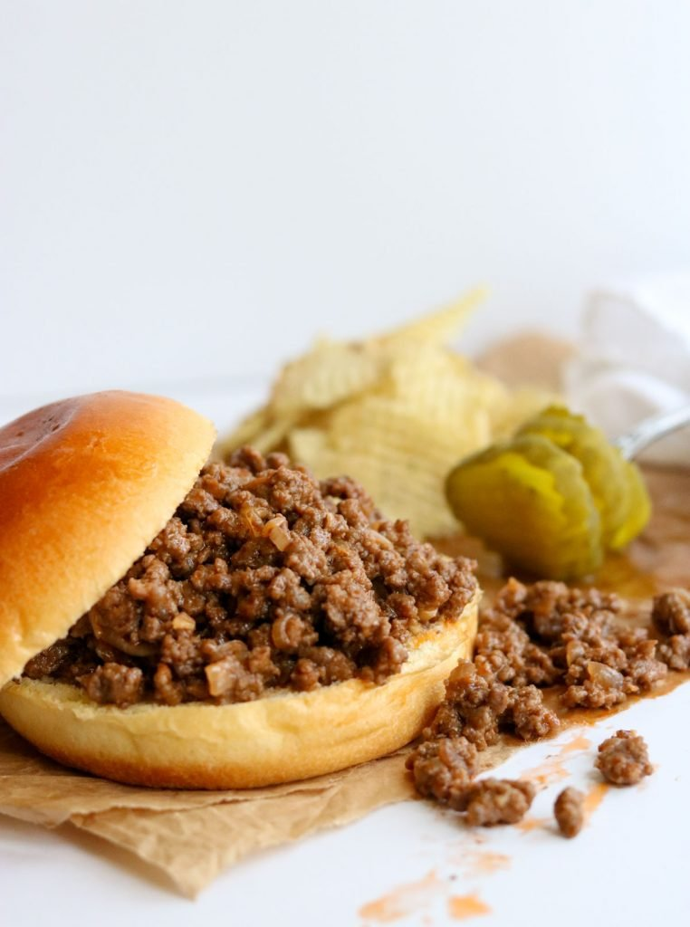 Homemade Sloppy Joe Sandwich with the bun to the side, pickles in the background
