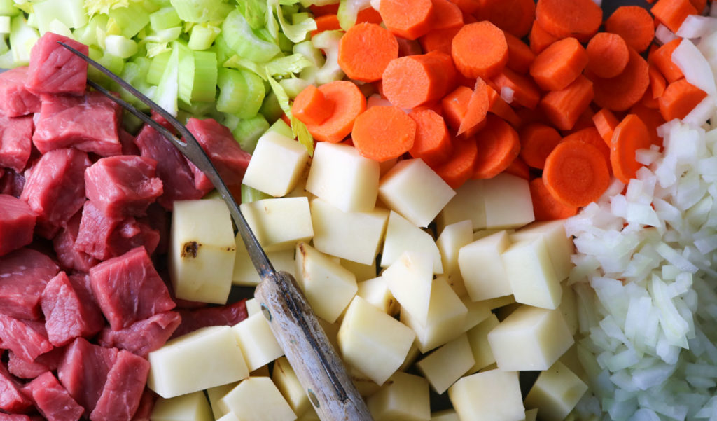 A close up picture of a lot of the ingredients that go into the steak soup: beef, potatoes, onions, carrots, and celery