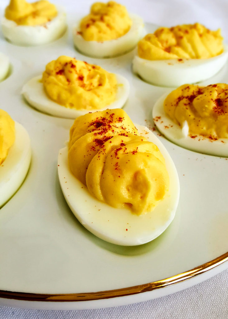 Deviled Eggs in an egg tray garnished with paprika