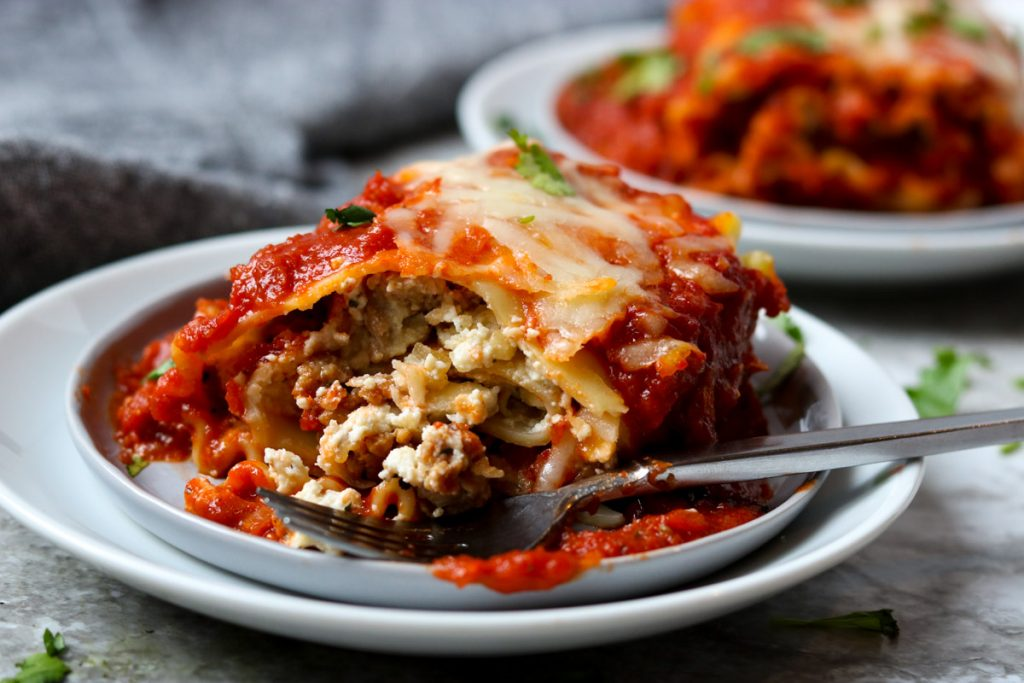 A lasagna roll up with a bite taken out of it showing all the layers and filling www.momsdinner.net