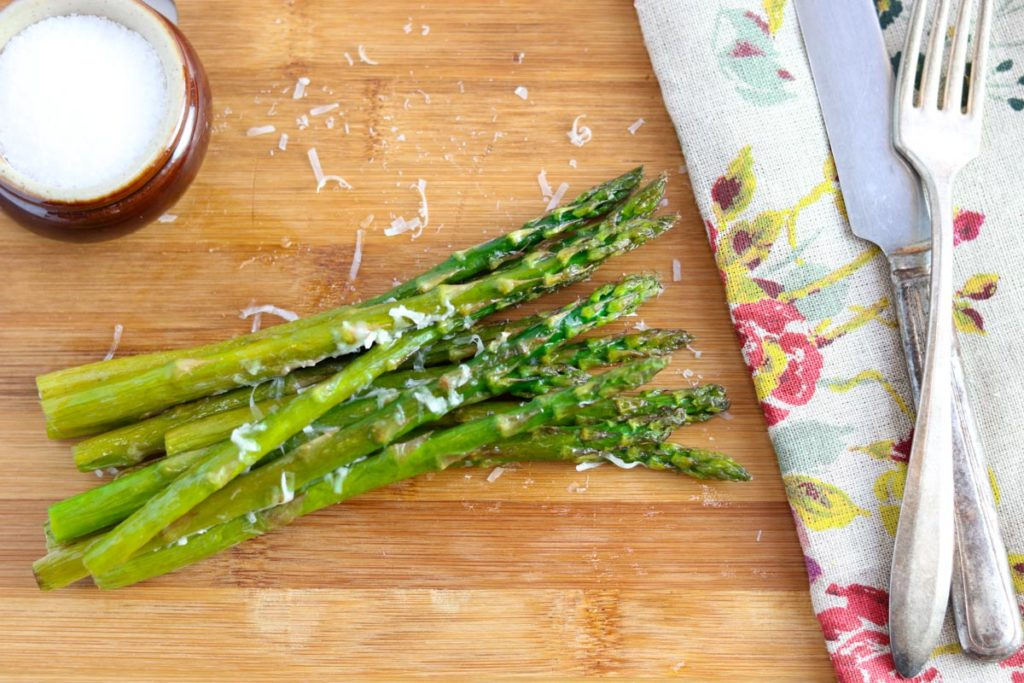 Oven Roasted Asparagus on a wooden cutting board with a salt cellar and a fork and knife on top of a floral napkin
