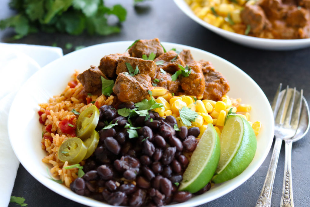 Instant Pot Burrito Bowl full of steak, beans, rice, corn and two lime wedges