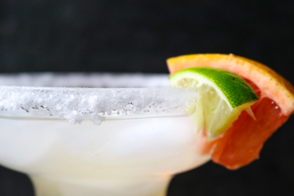up close picture of a margarita glass rim coated with sugar and salt and garnished with a lime and grapefruit