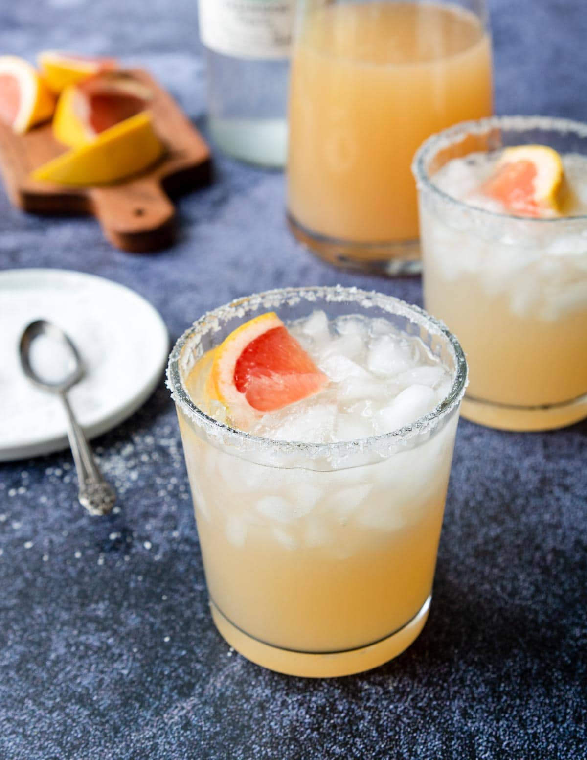 a glass of grapefruit margarita with a salty rim and a fresh grapefruit wedge