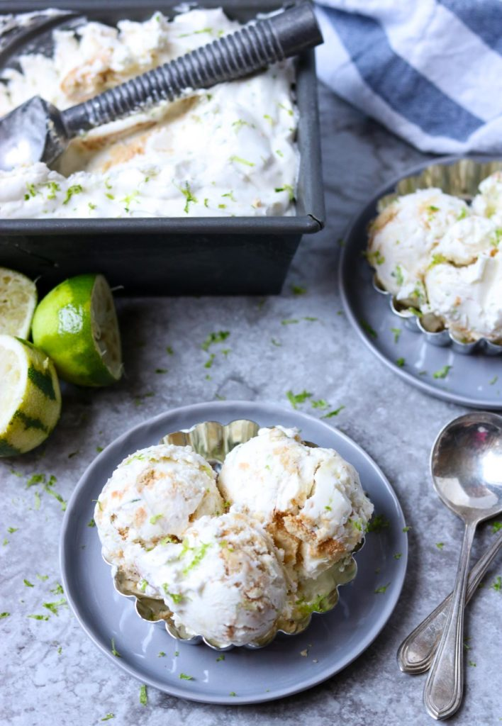 key lime ice cream with cookies mixed in sitting on a grey plate with spoons and limes to the side