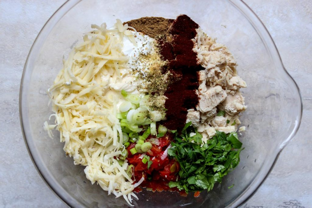 Creamy Chicken Taco filling ingredients all separate in a glass mixing bowl