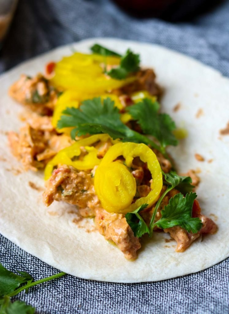 A flour tortilla laid out with creamy chicken taco filling, pepperoncinis and cilantro