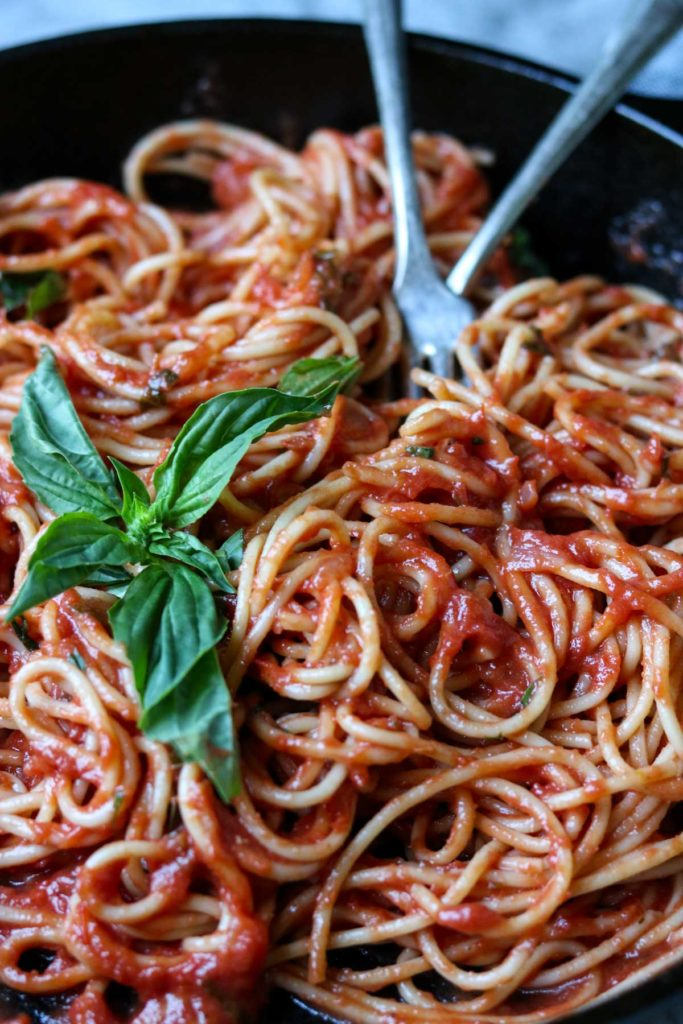 Easy Homemade Marinara Sauce with spaghetti in a pan with two forks, garnished with basil