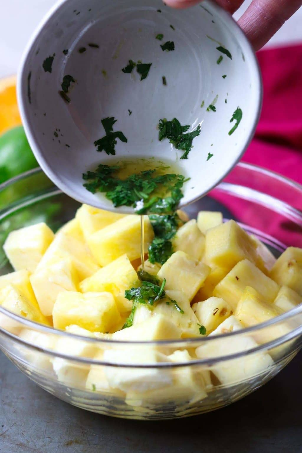 citrus herb glaze being poured over fresh cut pineapple