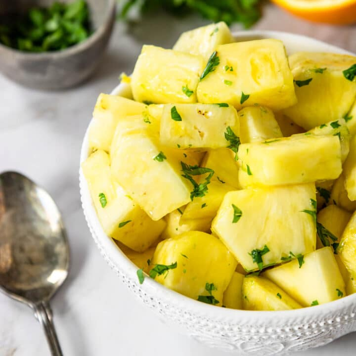 fresh pineapple in a bowl with a citrus cilantro glaze over top