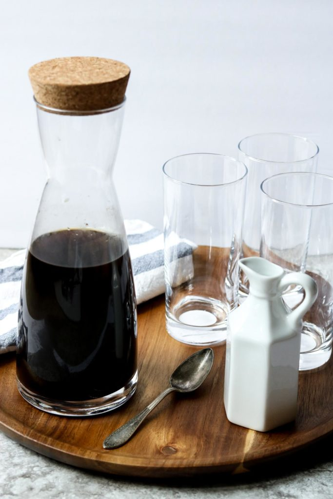 a tray with a coffee carafe three glasses and a milk carafe