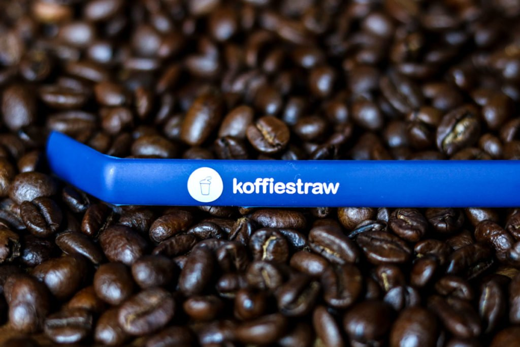 a plate of coffee beans with a blue koffiestraw