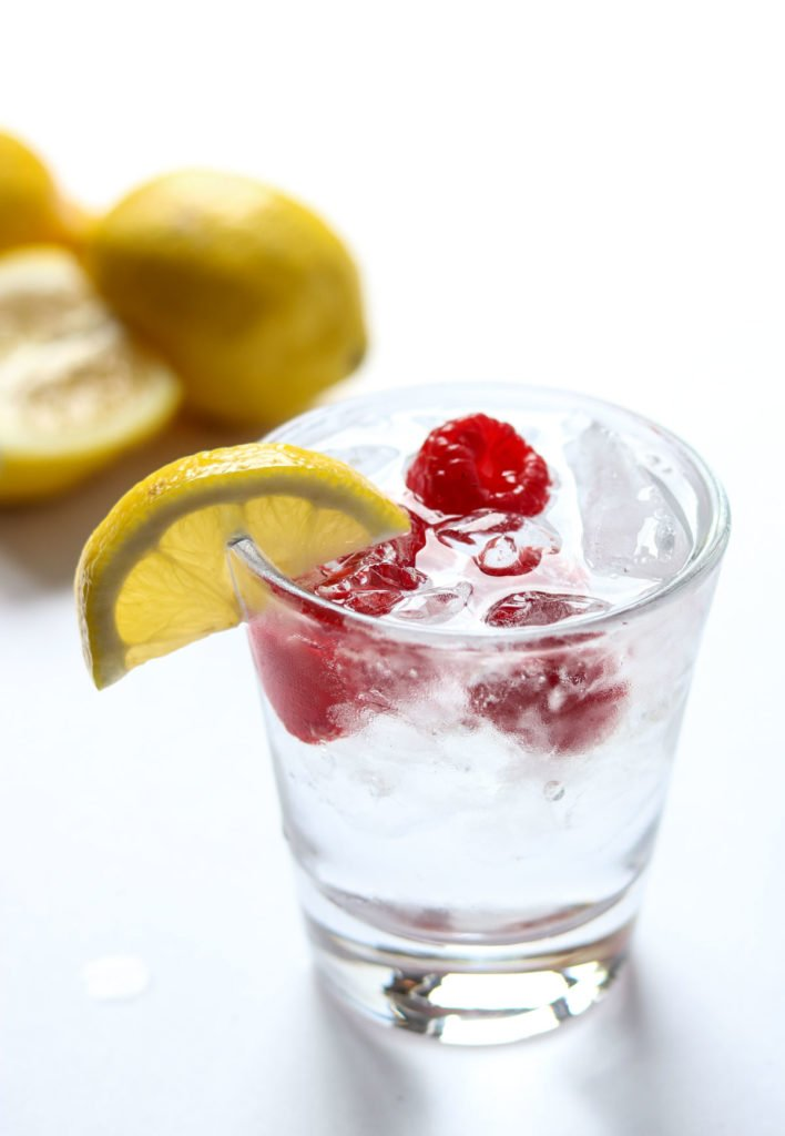 top of a cocktail that is garnished with lemon and raspberries