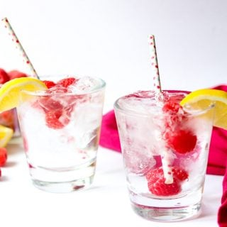 two raspberry vodka sodas garnished with raspberries and lemons