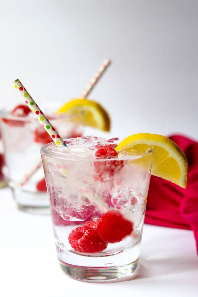 two raspberry vodka sodas with straws