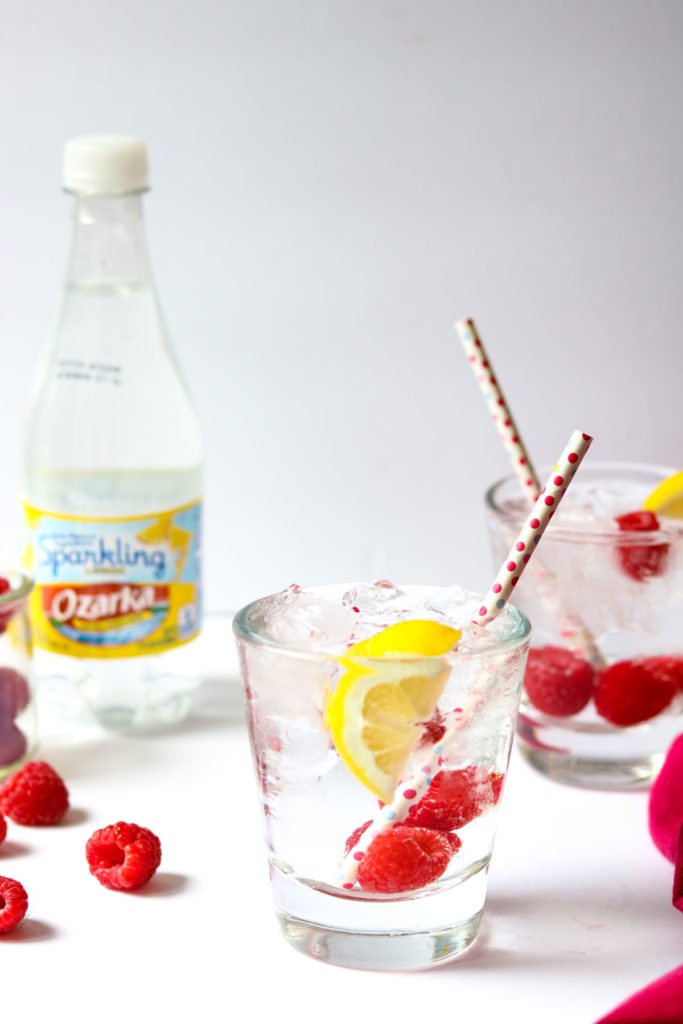 Raspberry vodka soda in glass garnished with fresh raspberries and lemon