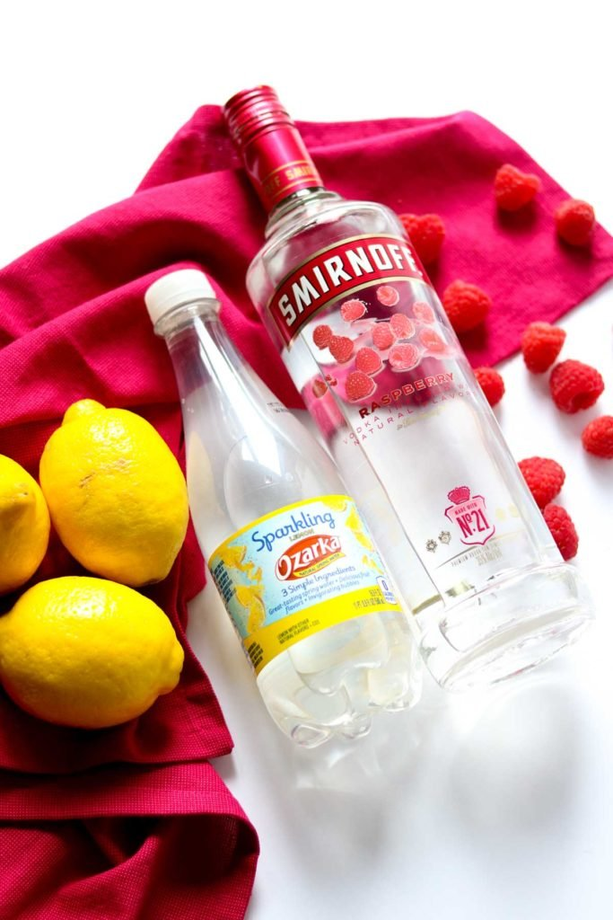 a bottle of raspberry vodka, lemon soda water, and lemons and raspberries