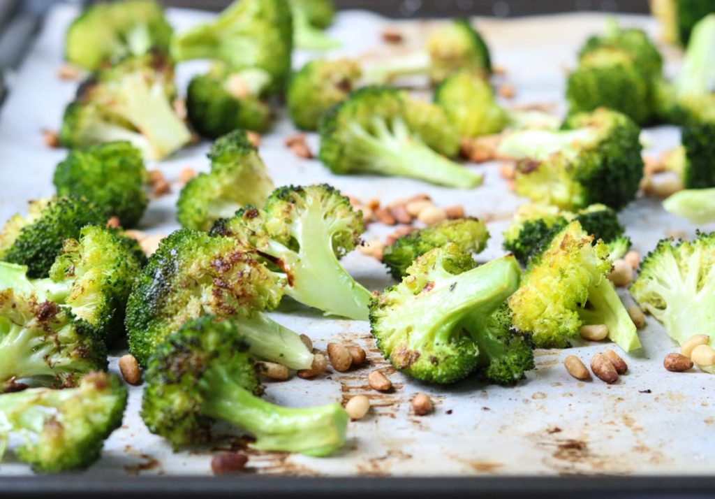 Oven Roasted Broccoli and pine nuts on a sheet pan lined with parchment paper