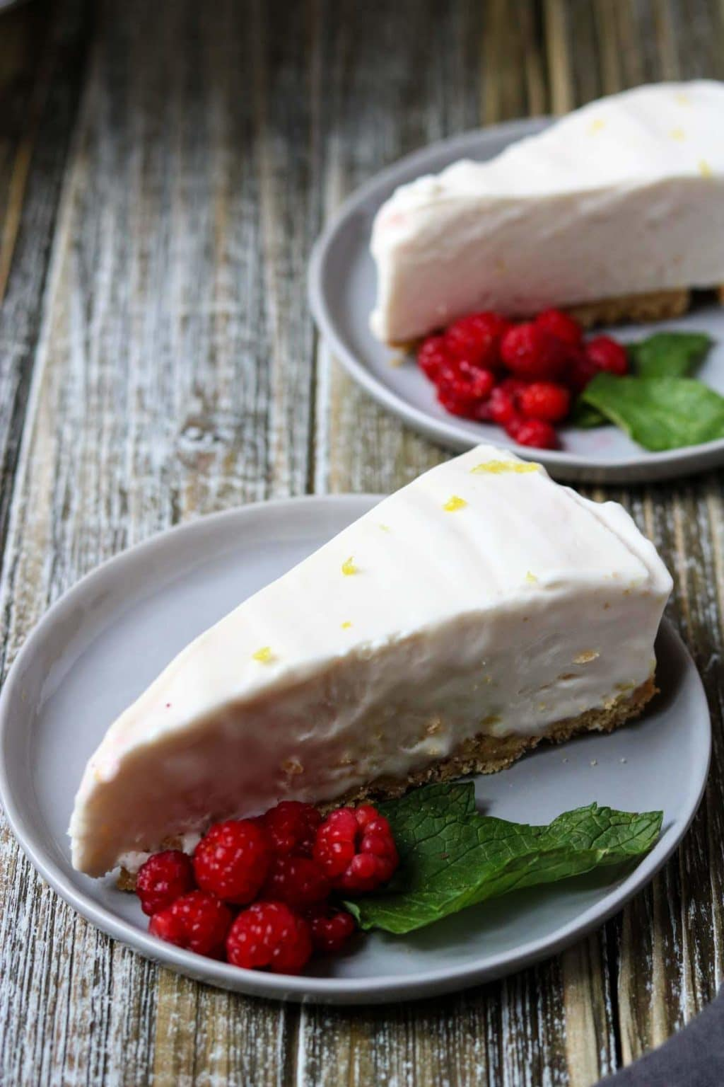 Two slices of Raspberry Lemonade Icebox Pie garnished with fresh raspberries and mint leaves