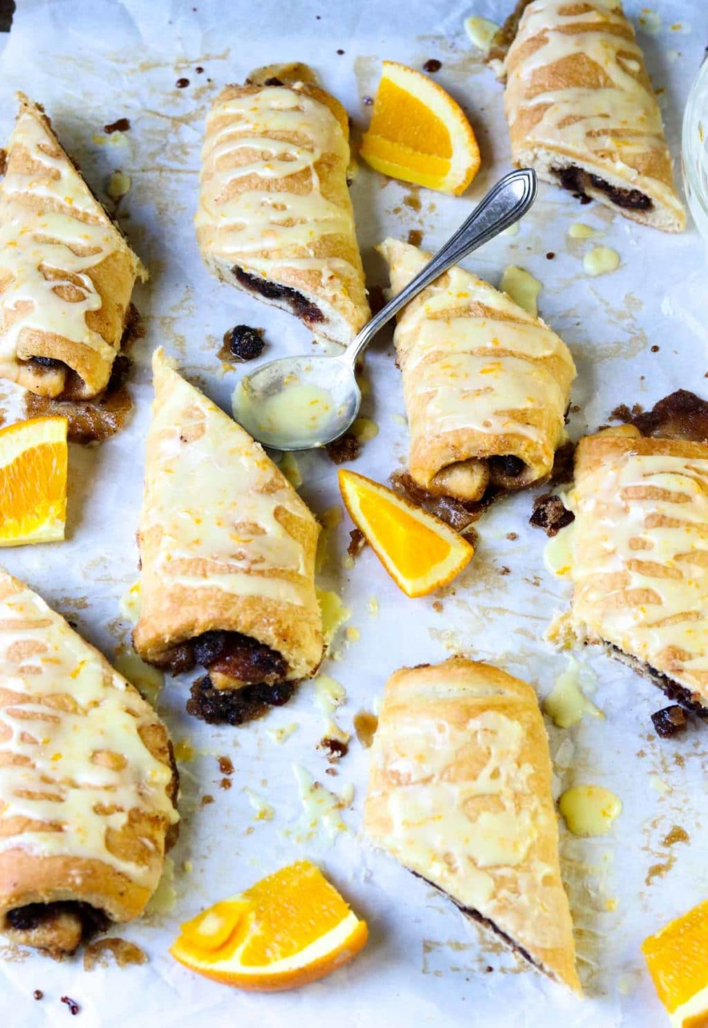 Cranberry Orange Sweet Rolls on parchment paper with fresh orange slices and a spoon full of frosting
