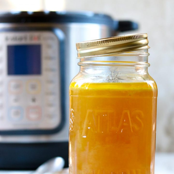 A mason jar full of chicken broth made in the instant pot