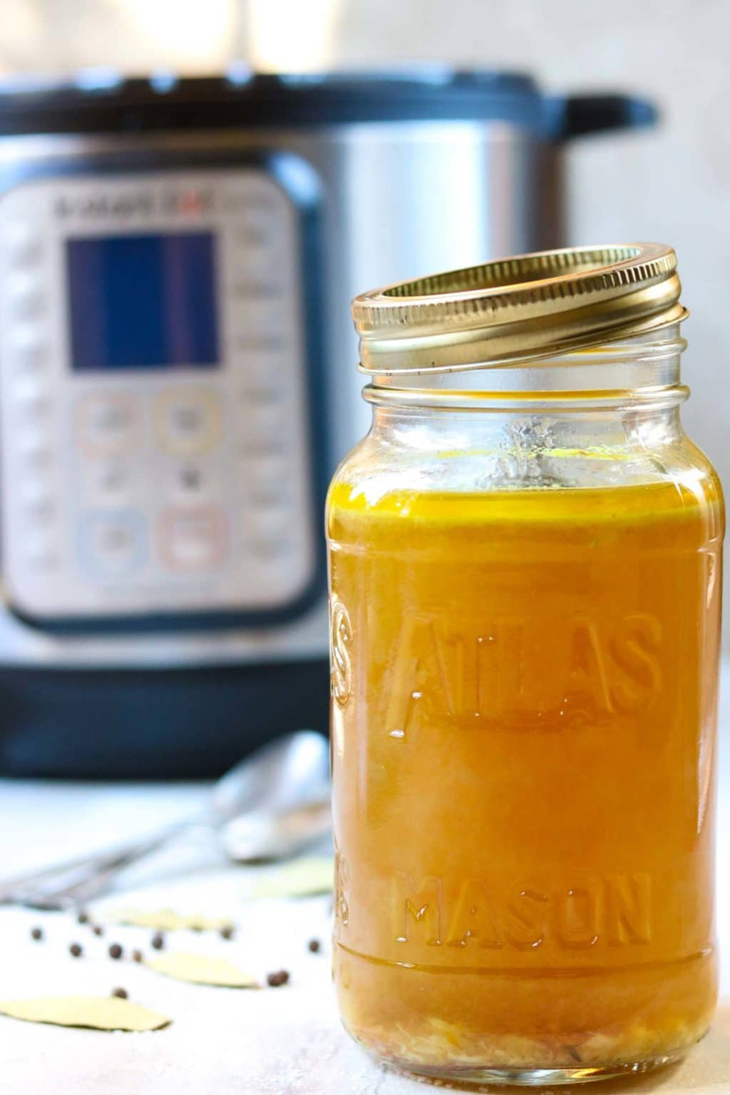 A mason jar full of Instant Pot Chicken Broth with an Instant Pot in the background