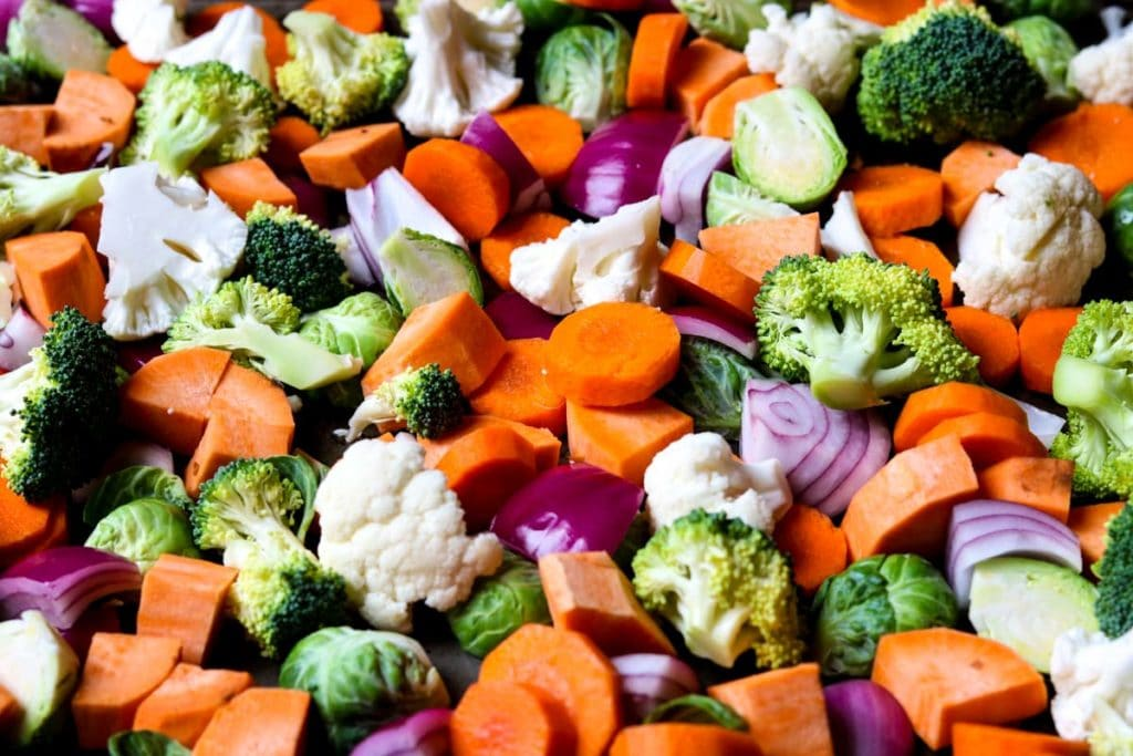 A beautiful tray of processed veggies- carrots, sweet potatoes, broccoli, red onions.