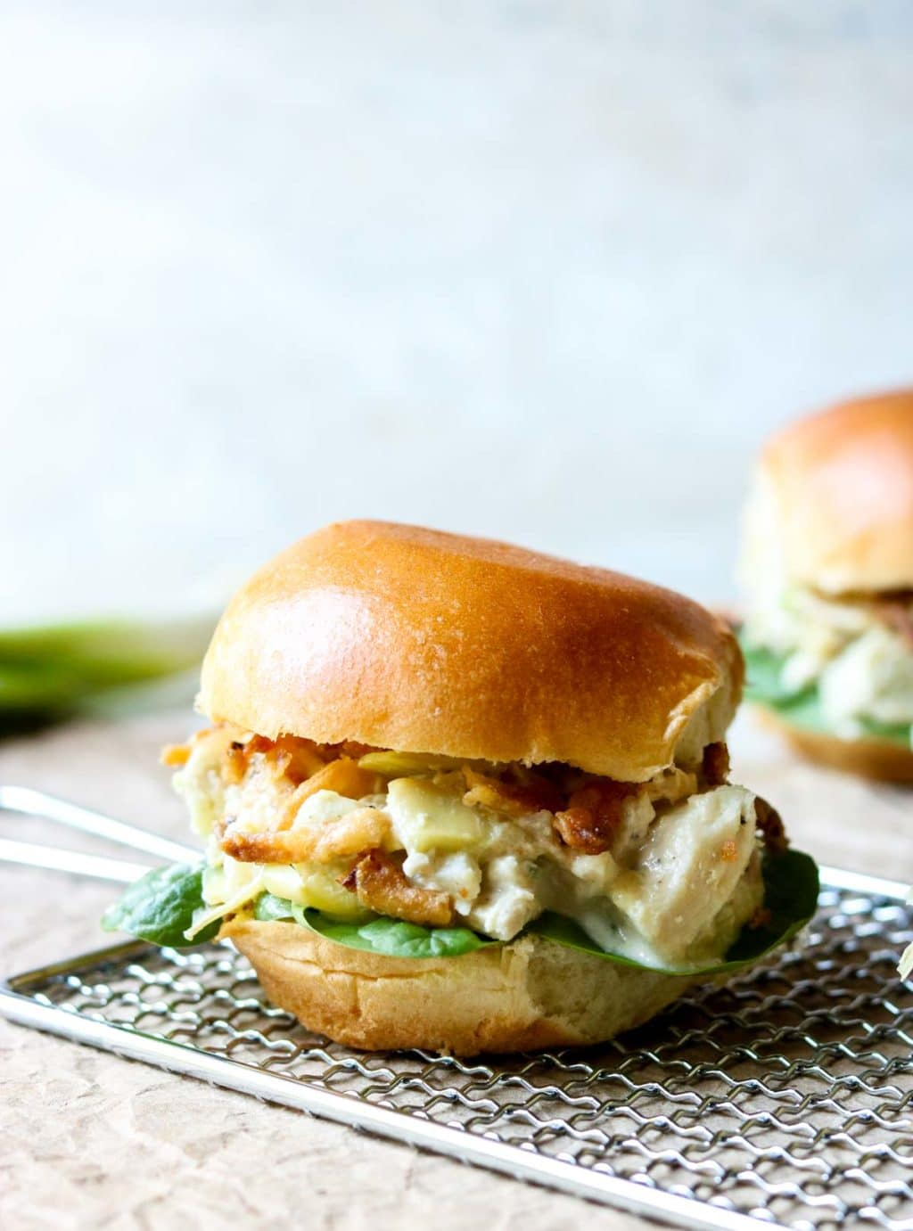 Chicken Salad Sandwich on a brioche bun sitting on a grater