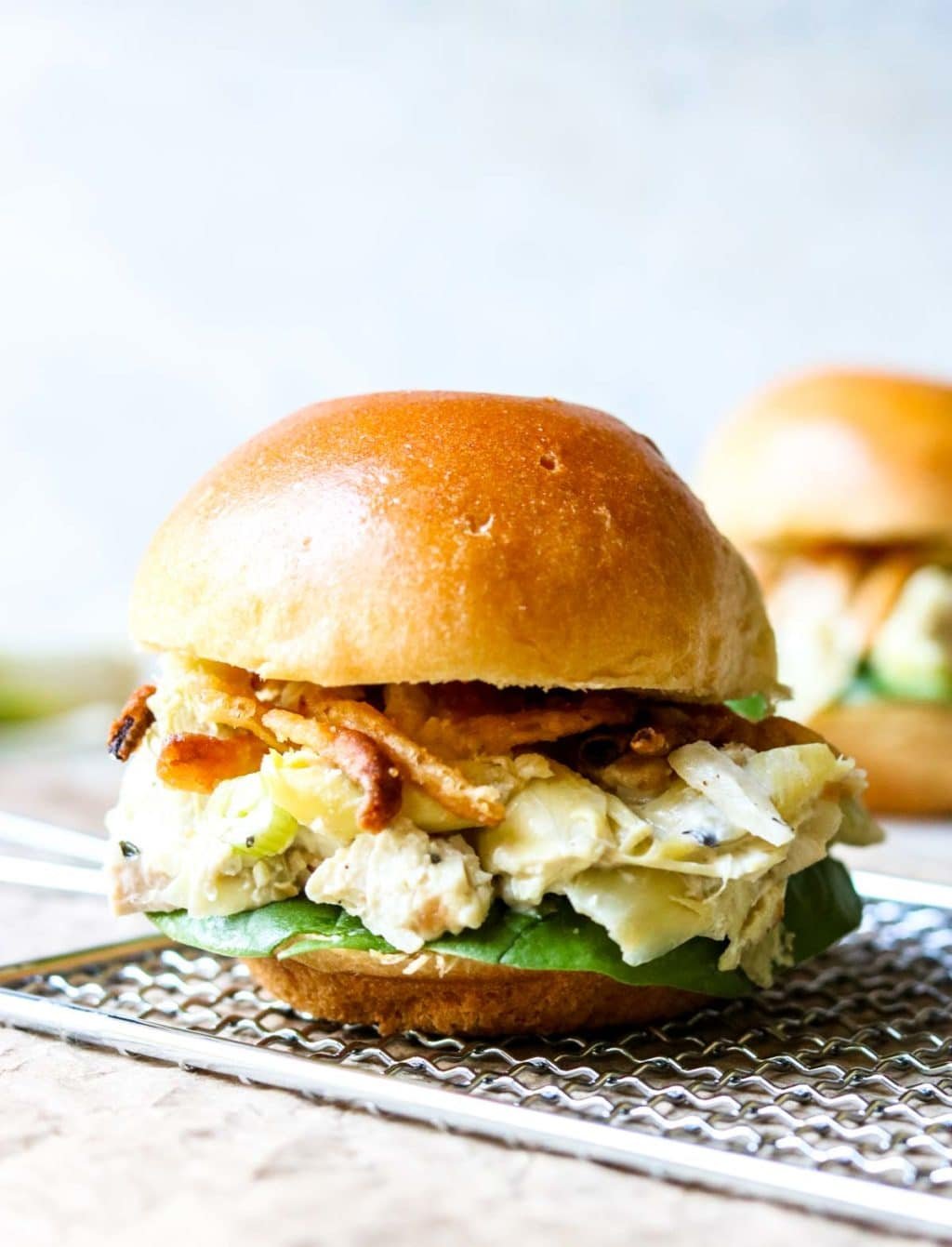 Hot Artichoke Chicken Salad on a brioche bun sitting on top of a grater